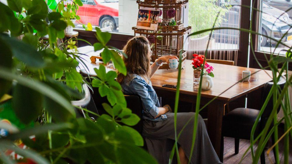 Femme prenant un café dans un intérieur vert